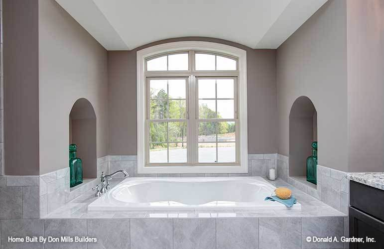 Arched inset wall niches filled with transparent green bottles flanked the drop-in bathtub.