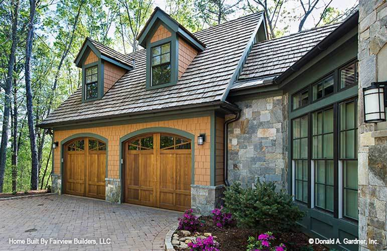 Home's double garage topped with a pair of charming dormer windows.