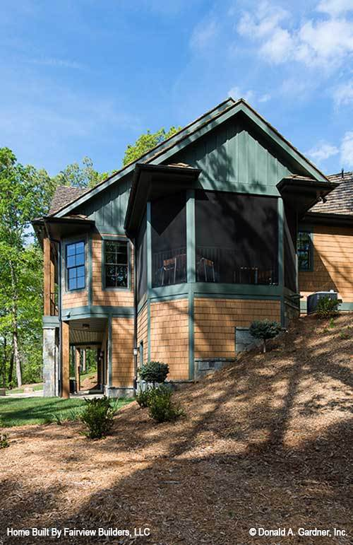The side exterior view features a screened porch situated above the sloping lot.