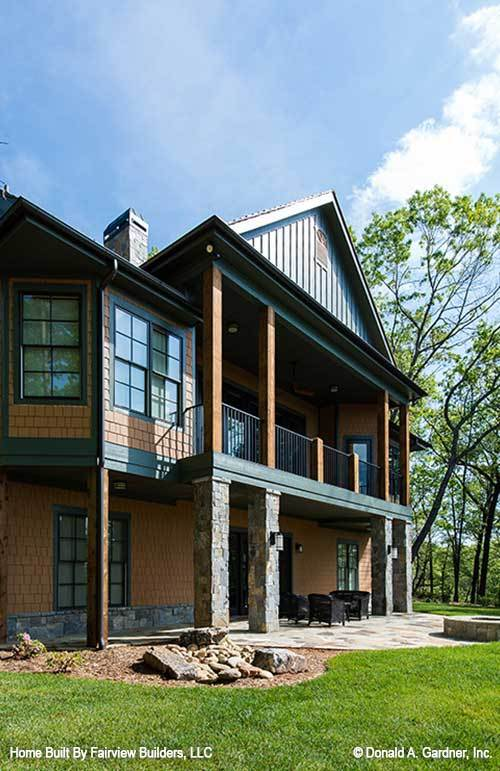 Wooden and stone columns frame the upper balcony and patio of this house.