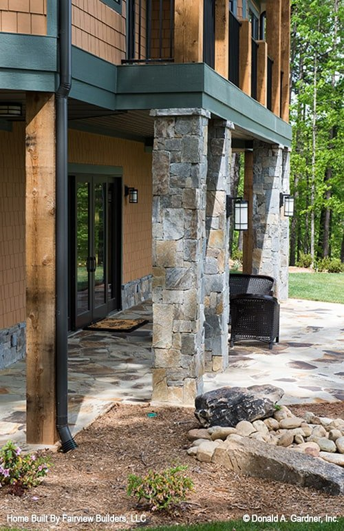 A closer look at the covered porch shows the outdoor sconces and wicker armchairs over flagstone flooring.