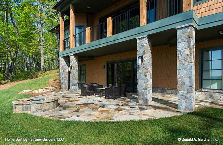 Multiple seating along with a built-in fire pit that matches the flagstone flooring fill the back porch.