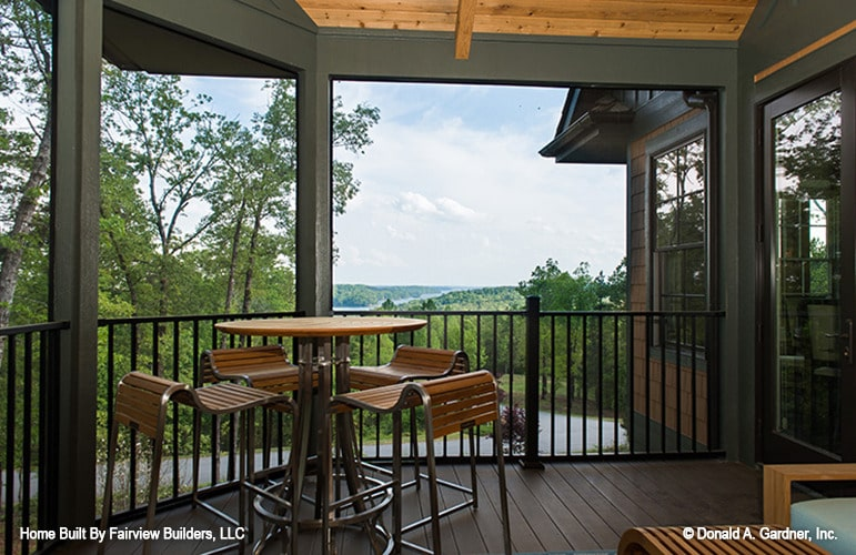 The screened porch is furnished with a round table and wooden seats.