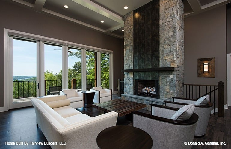 A large stone fireplace lined with a dark wood beam complete the living room.