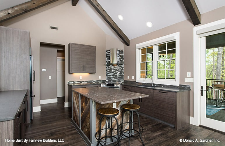 The kitchen has wooden cabinets, a breakfast island, and a cathedral ceiling framed with rustic beams.