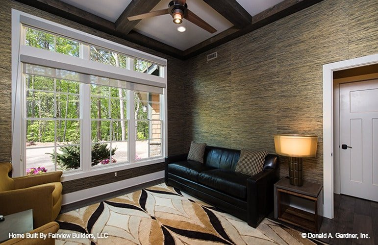 The entertainment room offers a black leather sofa, mustard armchairs, a patterned area rug, and a wooden side table topped with a drum lampshade.