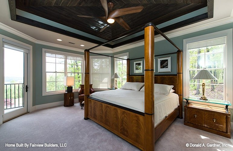 The primary bedroom showcases a wooden ceiling fan and a canopy bed flanked by glass top nightstands.
