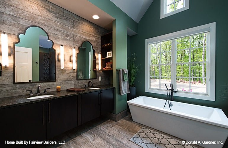Primary bathroom with a freestanding tub and a dual sink vanity paired with arched mirrors.