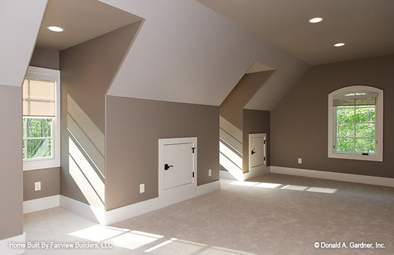 The bonus room has beige carpet flooring, vaulted walls, white-framed windows, and a regular ceiling fitted with recessed lights.