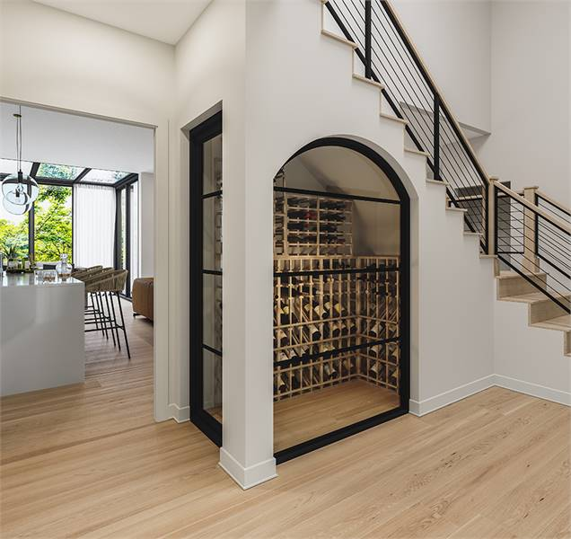 A wine cellar enclosed in black aluminum framed glass panels is placed below the staircase.