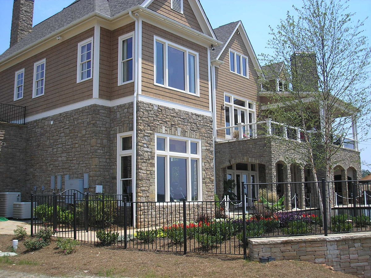 Angled rear view with covered porch and upper deck enclosed in wrought iron railings.