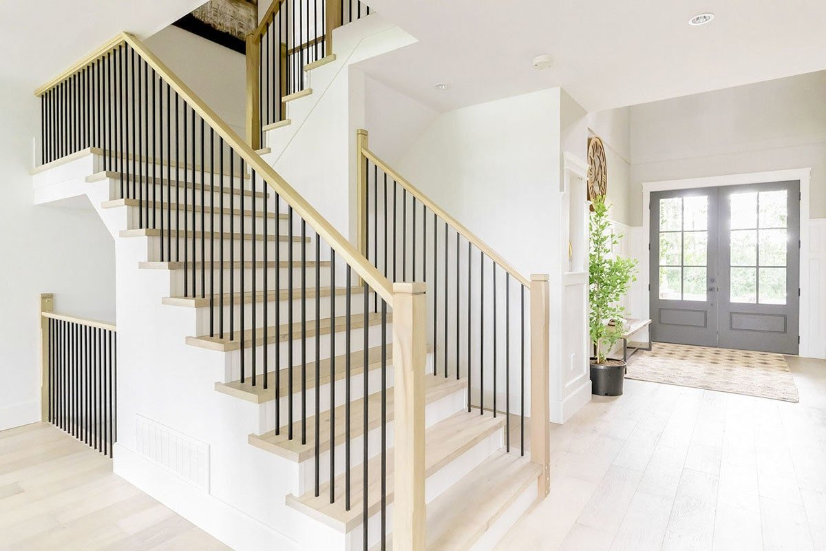 The foyer is filled with a staircase, french entry door, a wooden bench, fresh potted plant, and a patterned rug that lays on the wide plank flooring.