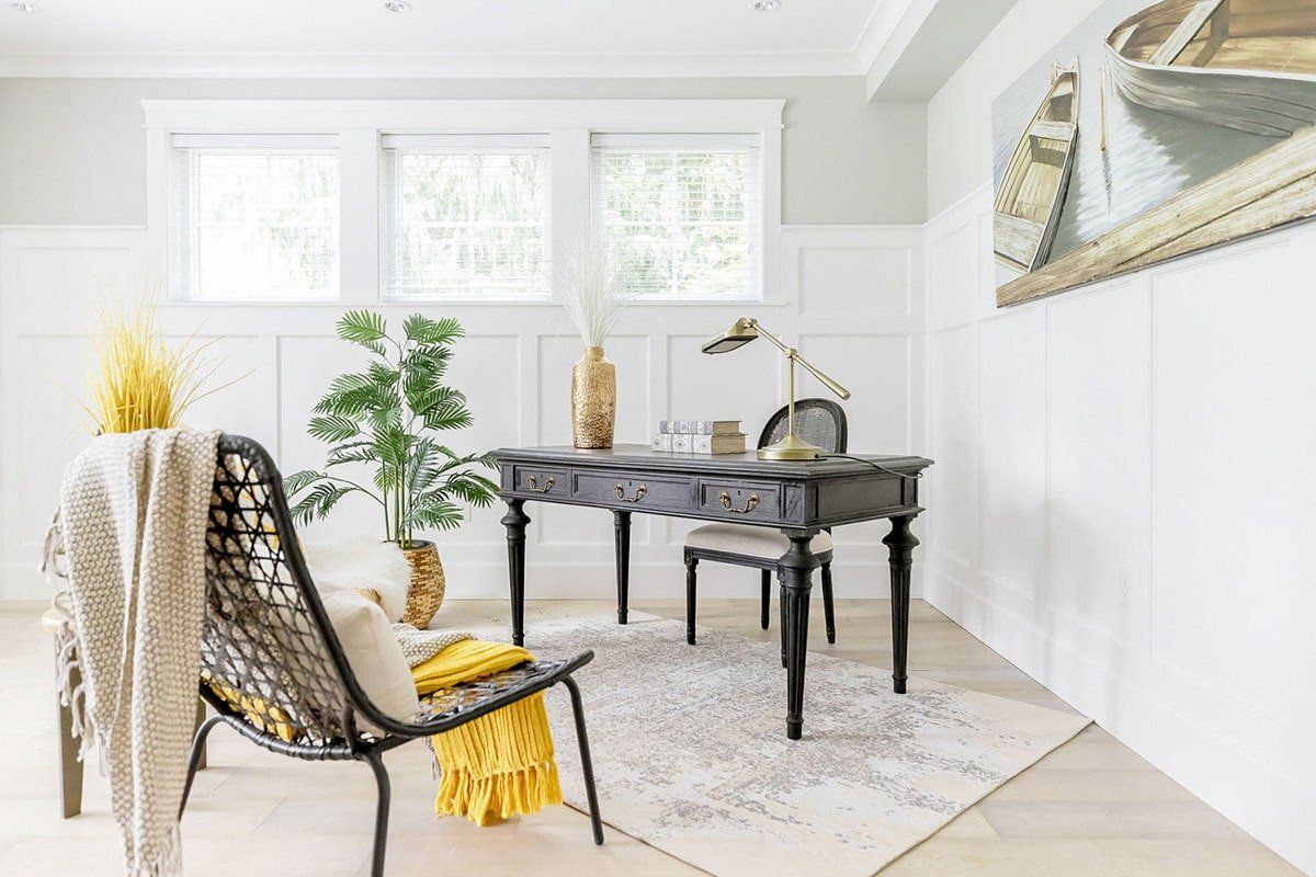 Study with cushioned and perforated chairs, dark wood desk, and a boat painting adorning the wainscoted walls.