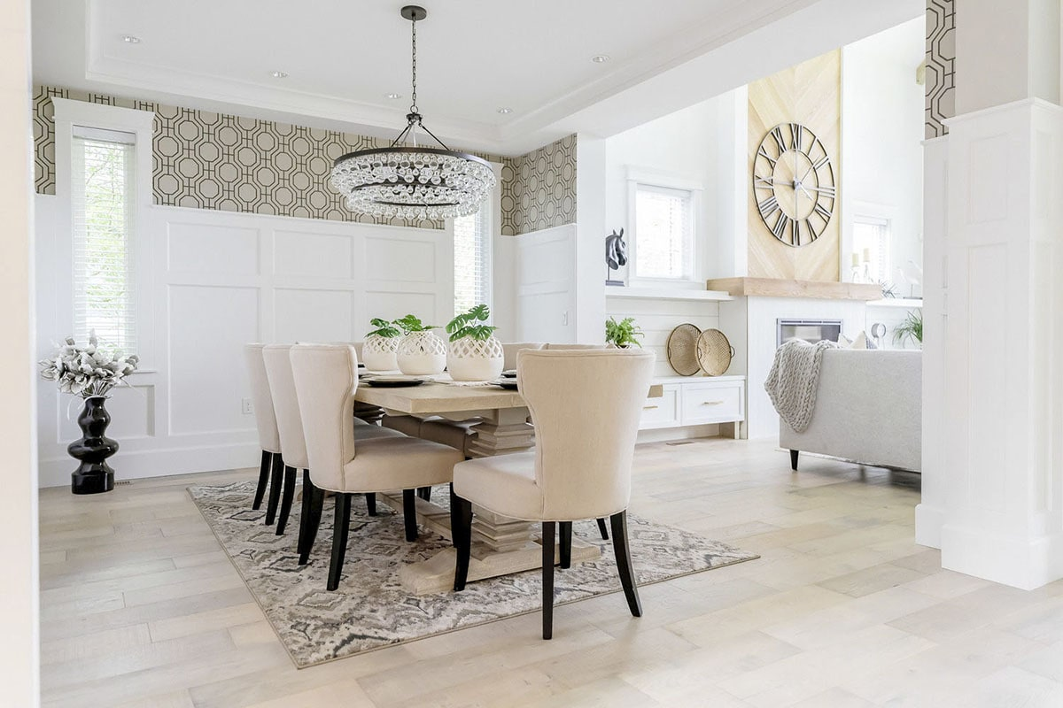 The dining room offers a patterned rug, beige wingback chairs, and a light wood dining table illuminated by a round chandelier.