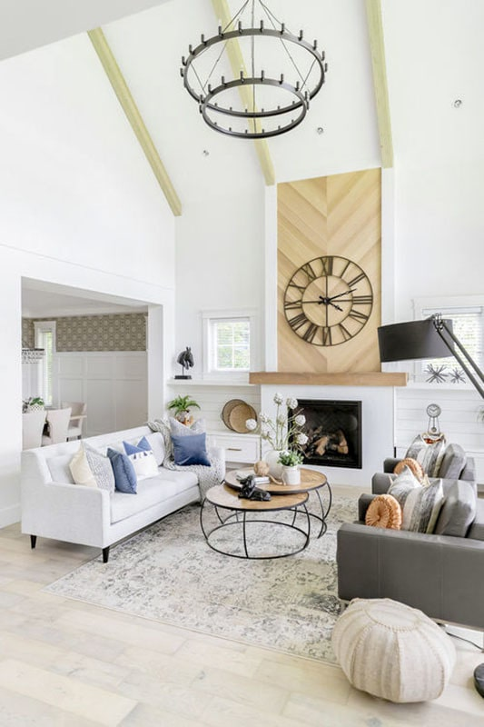 Living room with gray seats, modular coffee table, modern fireplace, and a two-tier chandelier hanging from the cathedral ceiling with exposed beams.