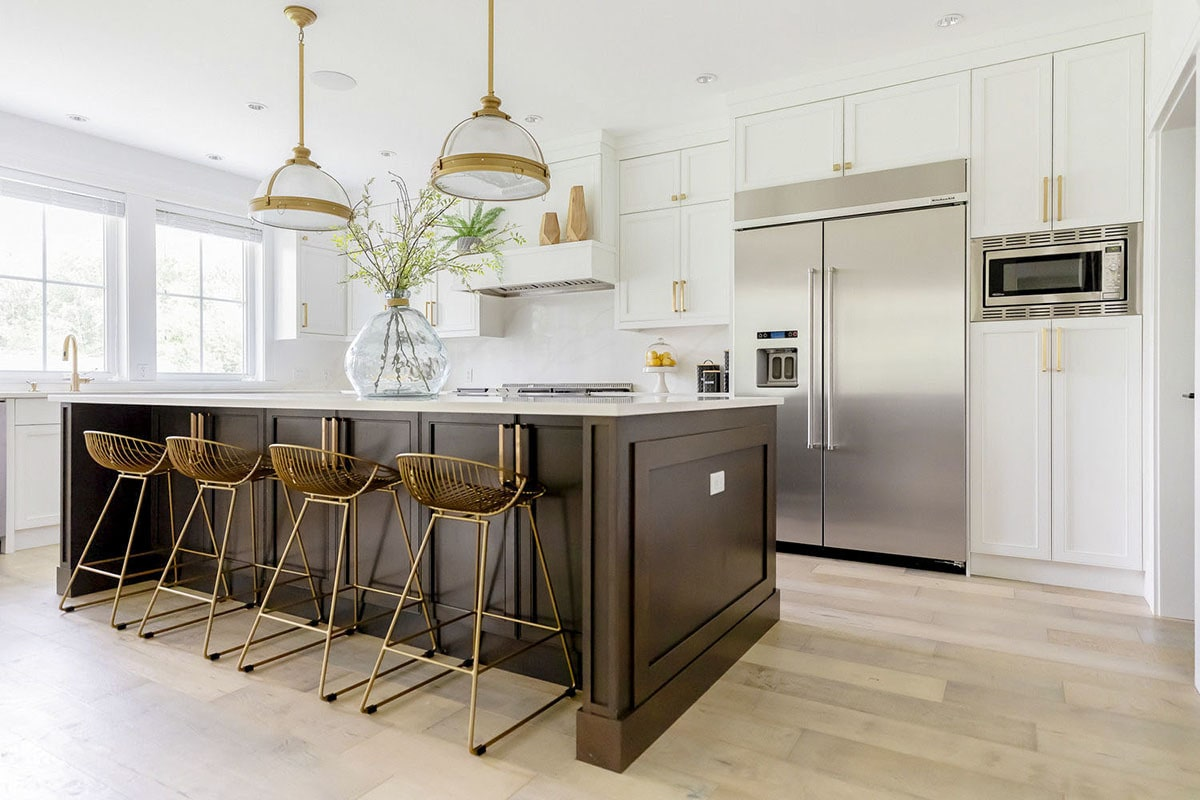 Kitchen with top of the line appliances, wooden island, and white cabinetry accented with brass hardware.