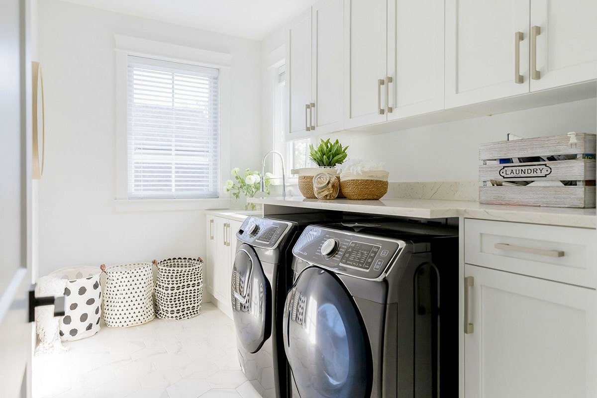 Utility with white cabinets, granite countertops, black front-load appliances, and patterned laundry bins.