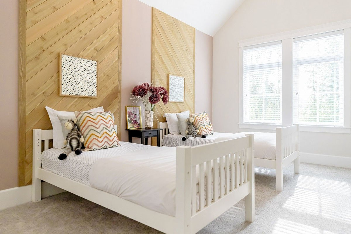 This bedroom offers two beds and a dark wood center nightstand topped with a frame and vase.
