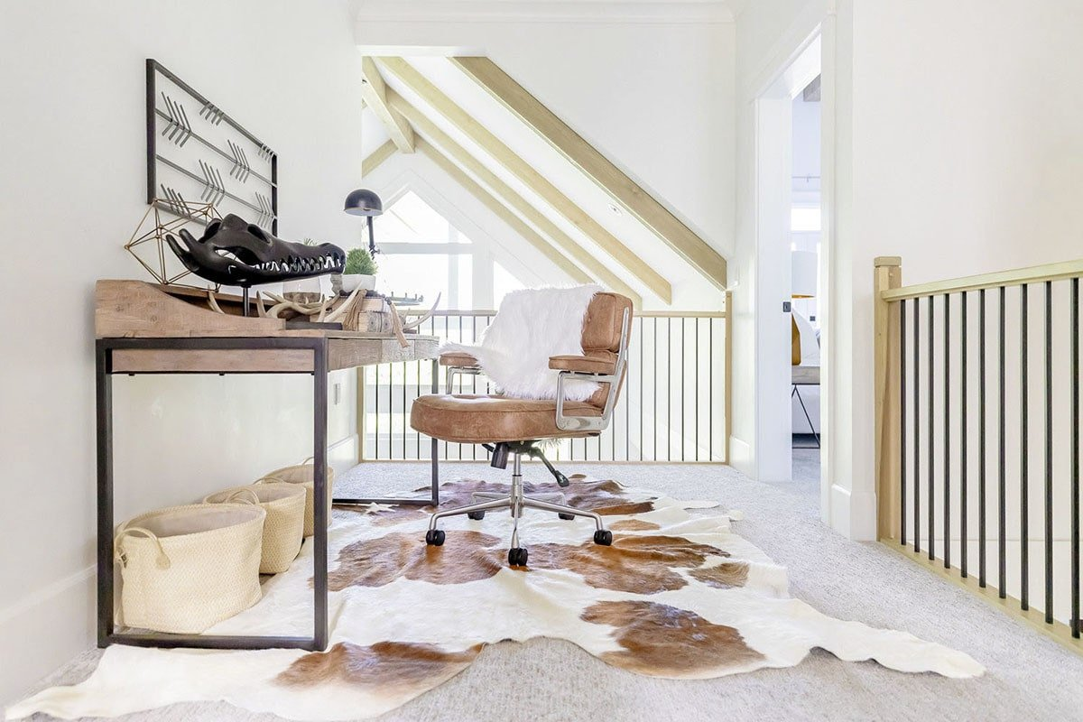 Second-floor loft that doubles as an office showcasing a wooden desk and leather swivel chair over a cowhide rug.