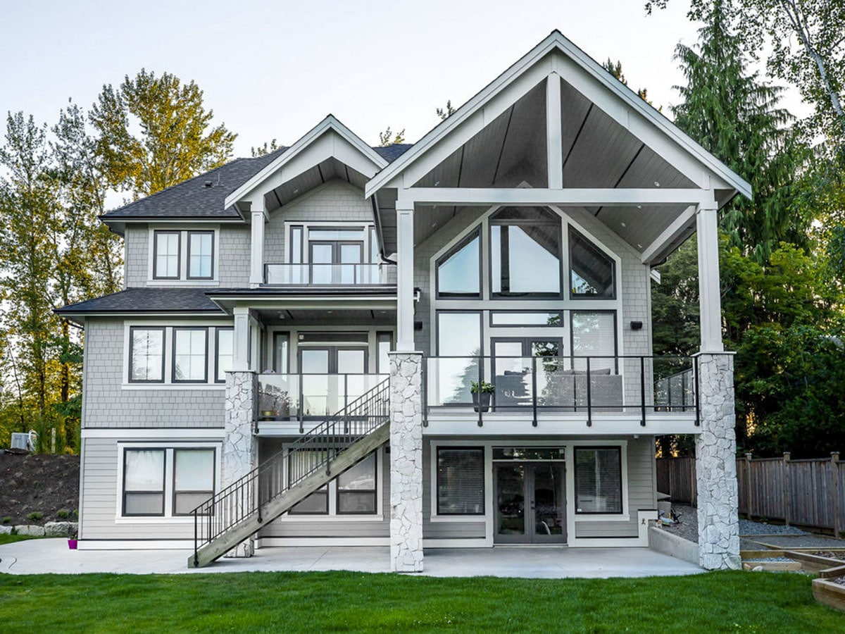 Rear exterior view showing the stone columns and multiple decks enclosed in glass railings.