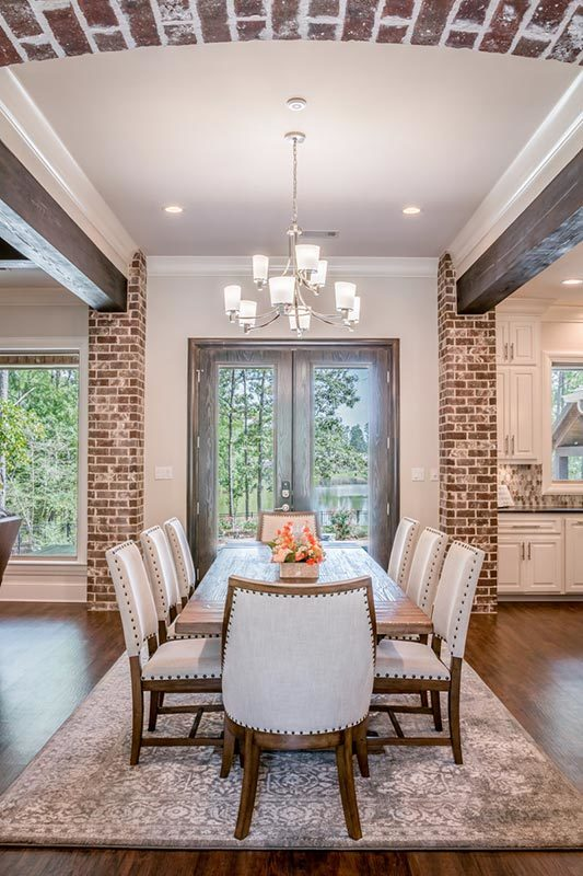 The dining area offers a distressed rug, beige upholstered chairs, and a rectangular dining table well-lit by a glass chandelier.