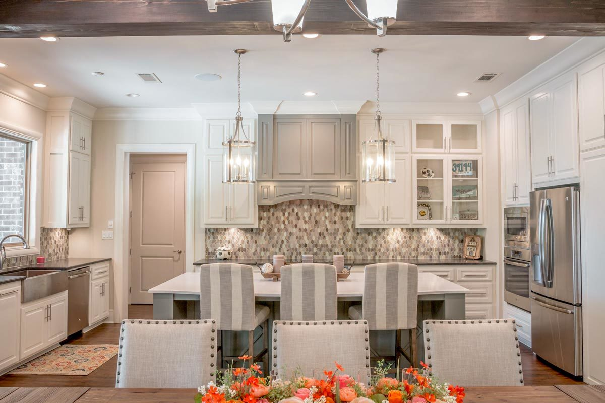 The kitchen is equipped with marble and granite countertops, stainless steel appliances, a farmhouse sink, and white cabinetry.