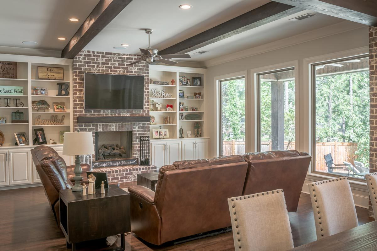 The living room offers brown leather seats, dark wood tables, and a brick fireplace flanked with white built-ins.