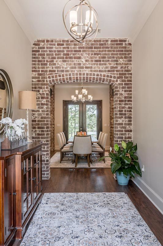 The foyer has a wooden console table, spherical pendant, patterned rug, and a brick archway leading to the dining room.