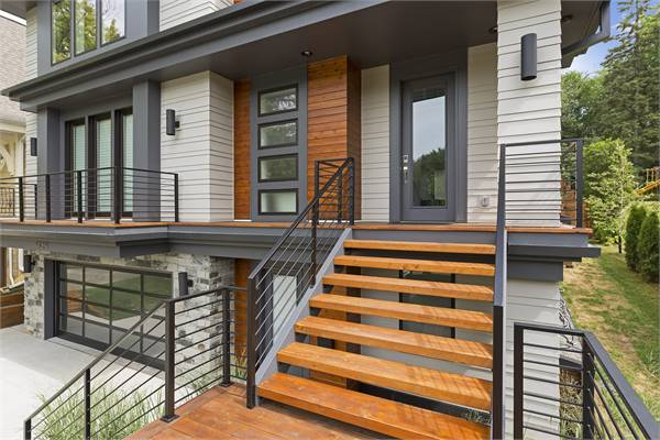 Home entry with a glass front door complemented with a modern staircase.