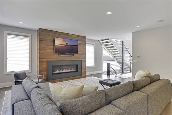 The living room offers L-shaped sectional, gray seats, and a glass-enclosed fireplace with a TV on top.