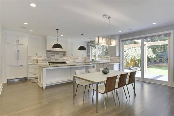 Eat-in kitchen with a sliding glass door on the side that leads out to the backyard.