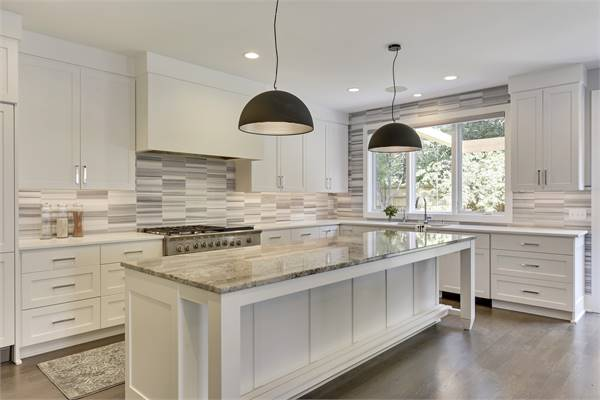 The kitchen is equipped with stainless steel range, white cabinets, and a center island illuminated by black dome pendants.