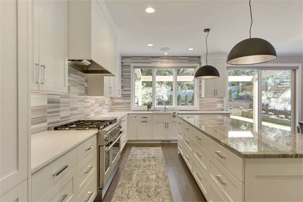 Linear mosaic tile backsplash and an undermount sink under the three-panel window complete the kitchen.