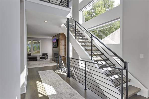 The foyer has a modern staircase and a distressed runner that lays on the hardwood flooring.