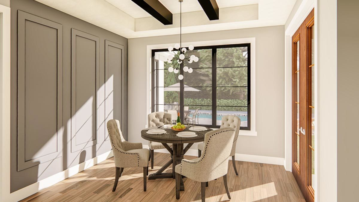 Breakfast nook with a round dining set, gray wainscoted accent wall, and a tray ceiling lined with rustic beams.