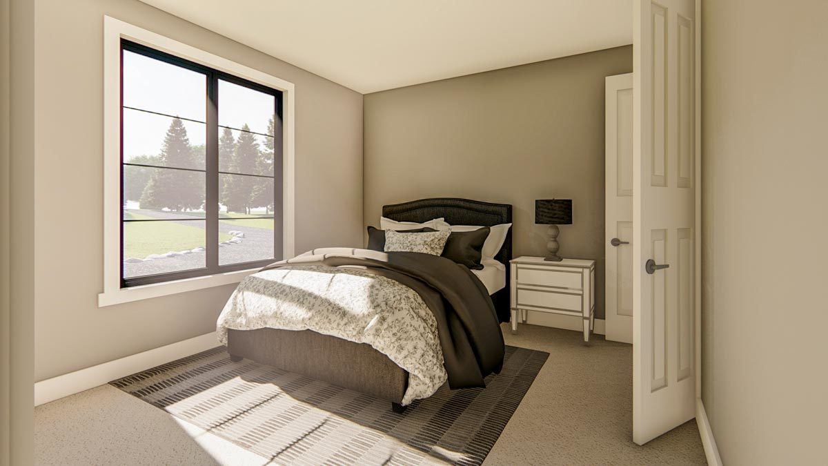 This bedroom is brightened by natural light streaming in from the black aluminum-framed windows.