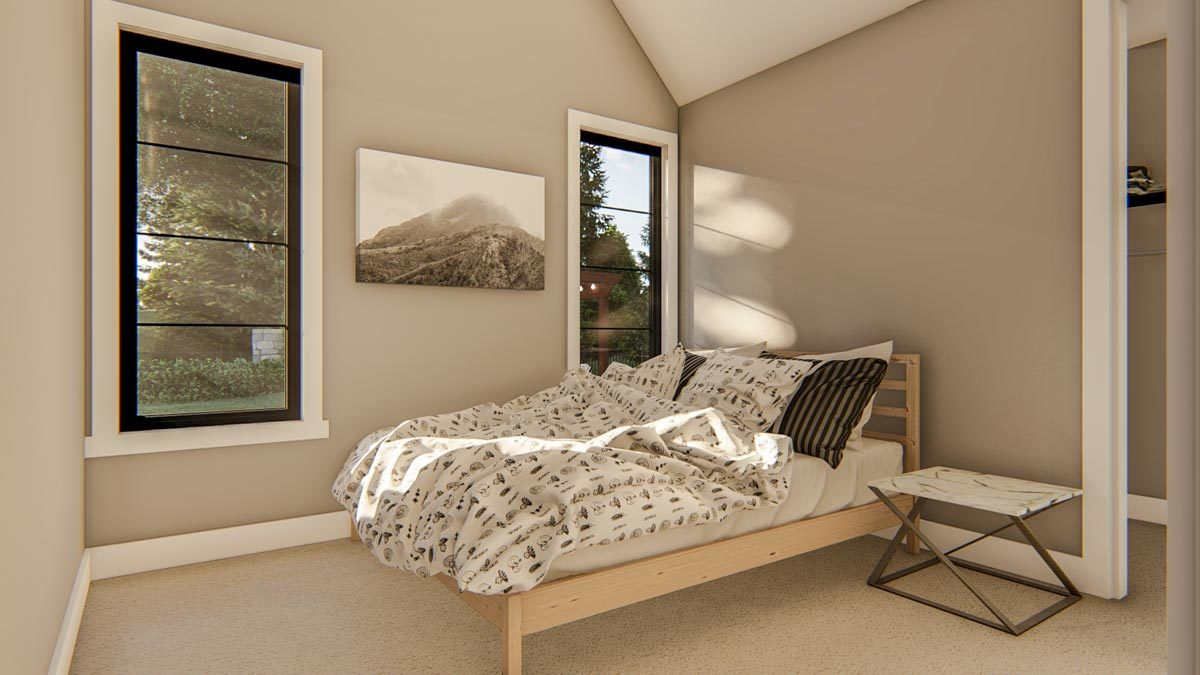 Metal nightstand, light wood bed, and a mountain artwork fill this bedroom.