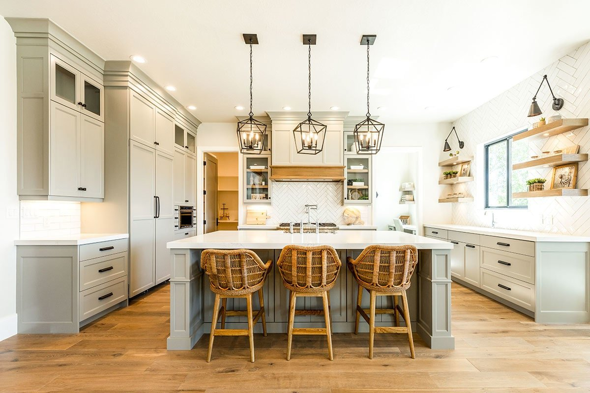 Kitchen with light gray cabinets, floating shelves, herringbone tile backsplash, and a center island paired with wooden counter chairs.