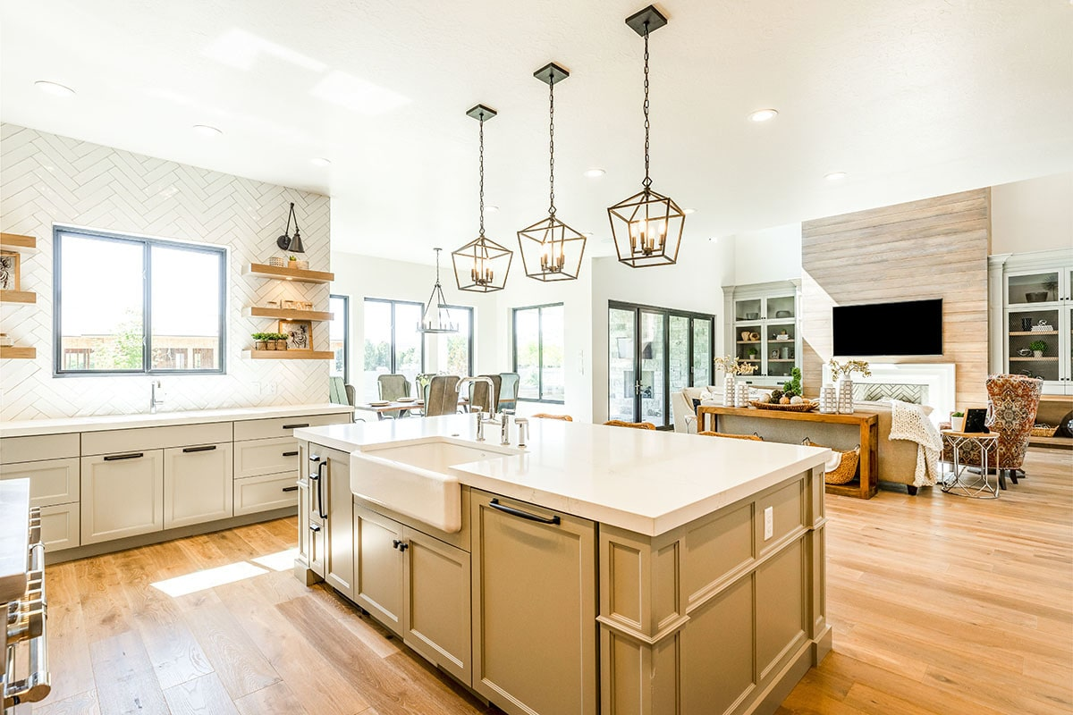 Three caged pendant lights hang above the center island that's fitted with a farmhouse sink.