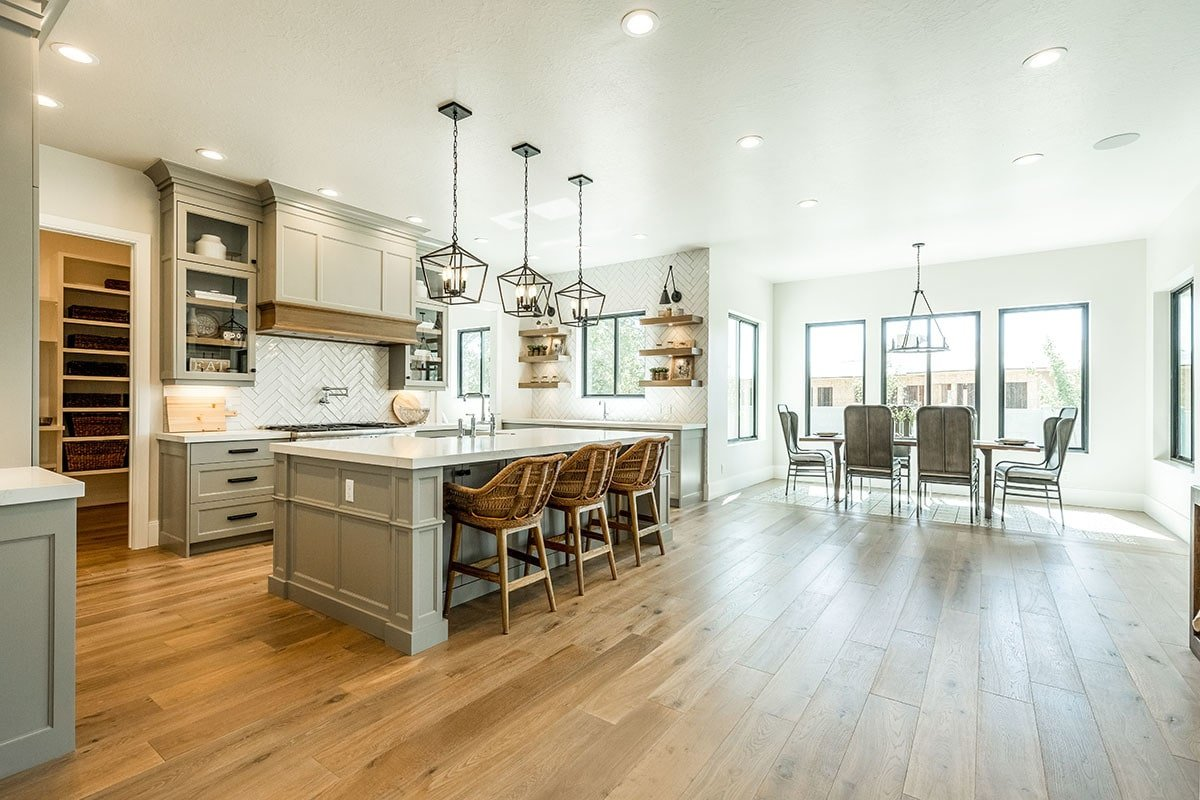 Kitchen and breakfast nook with wide plank flooring and white regular ceiling mounted with recessed lights.