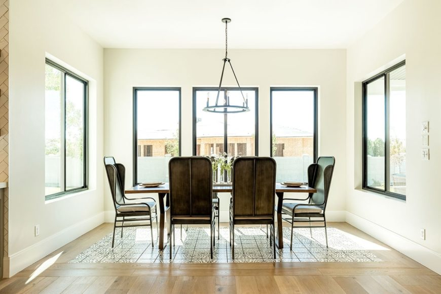 The dining room offers cushioned chairs and a rectangular dining table illuminated by a round chandelier.