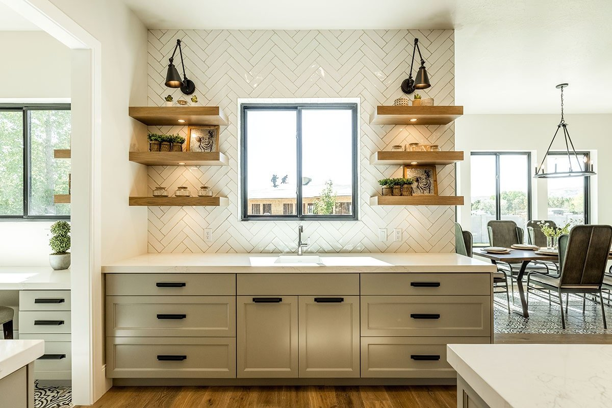 Wooden floating shelves flanked the aluminum-framed window that's fixed above the undermount sink.