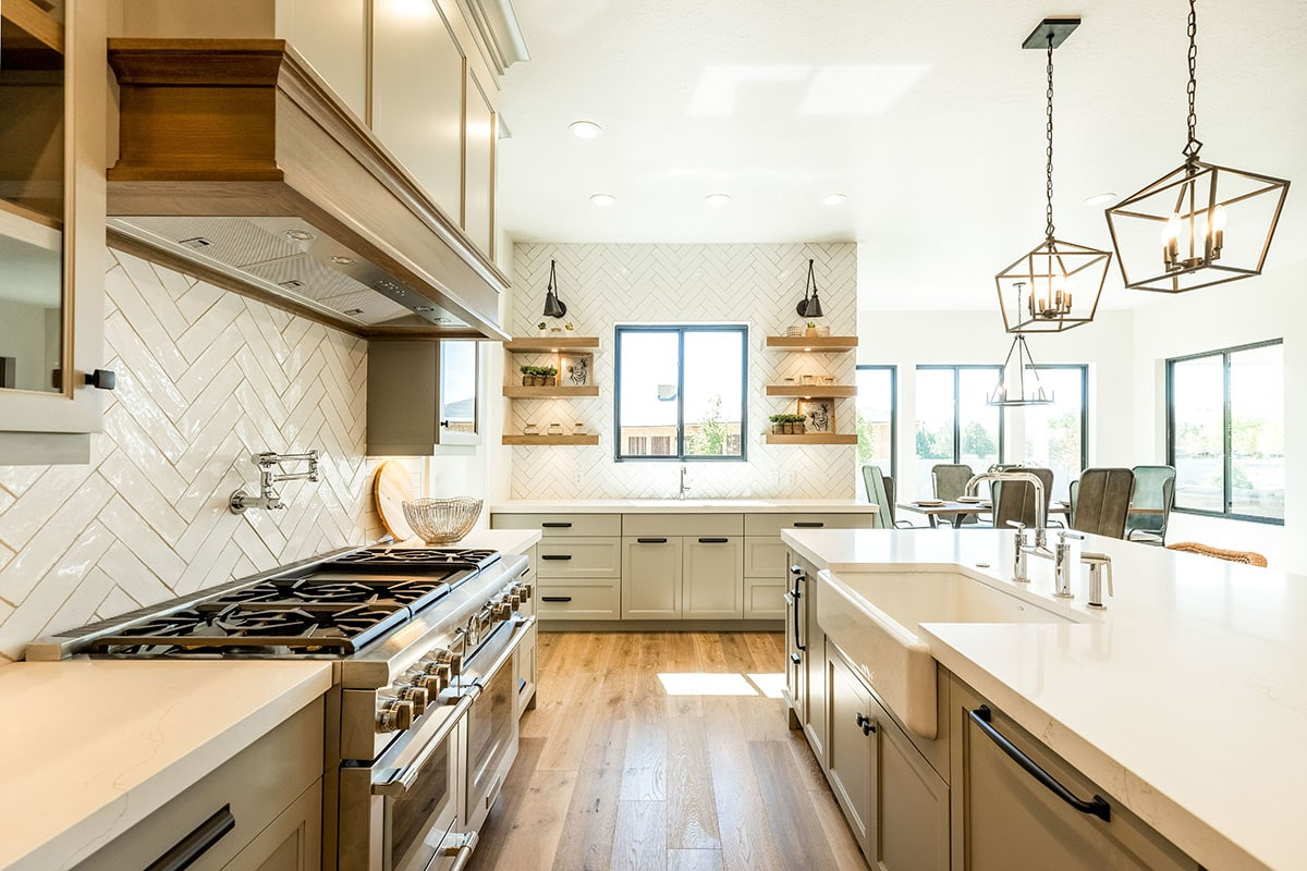 Double oven range, a bespoke vent hood, and white marble countertops complete the kitchen.