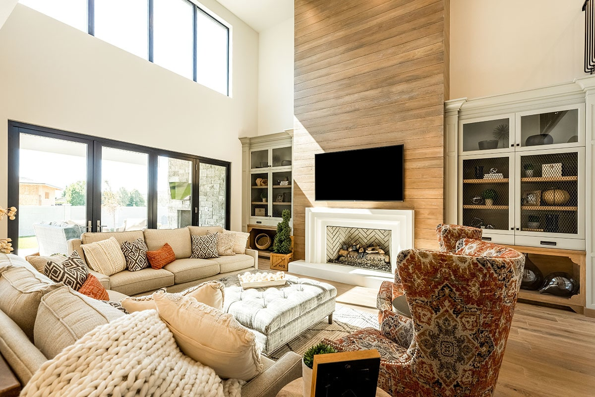 Living room with beige sectionals, printed wingback chairs, a tufted ottoman, built-in cabinets, and a fireplace with a wall-mounted TV on top.
