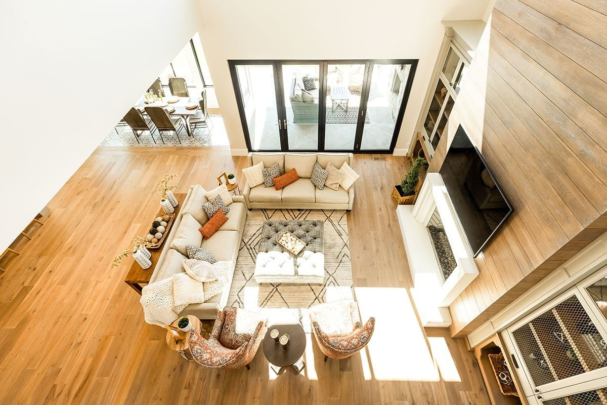 Top view of the living room showing the rich hardwood flooring along with glass doors on the side that open to the covered patio.