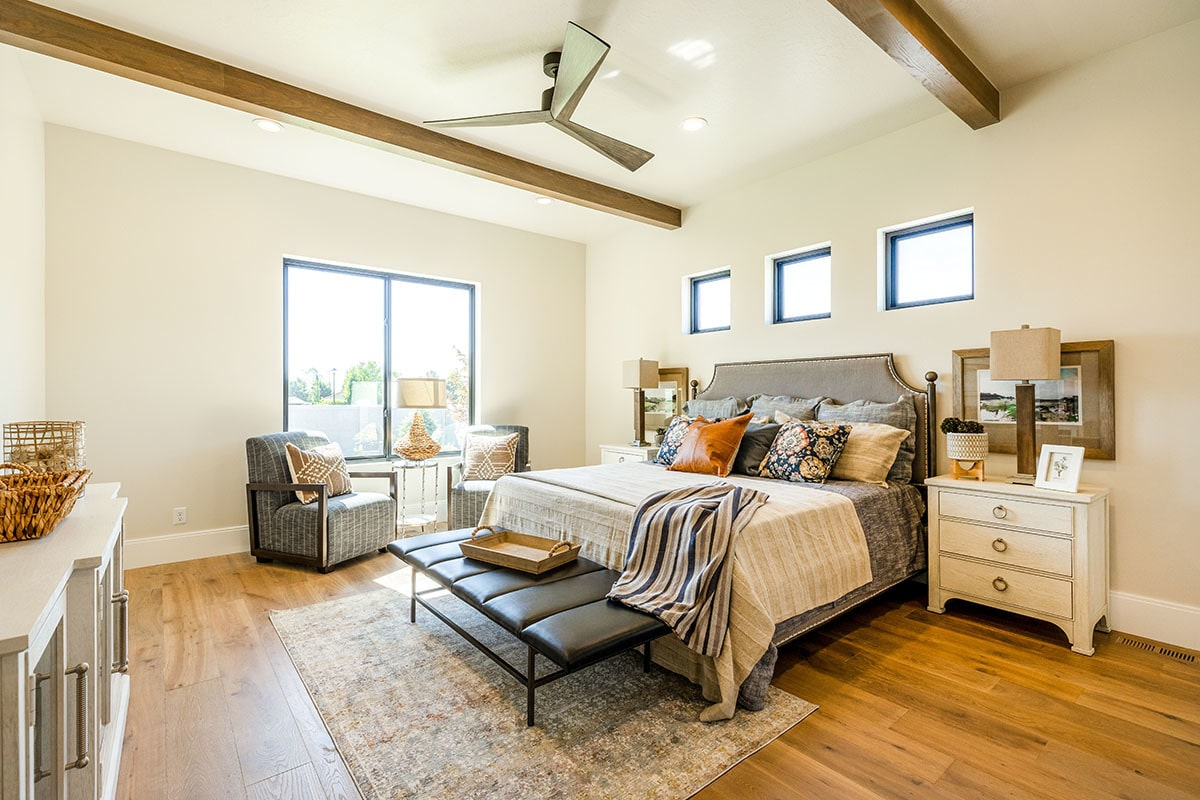 Primary bedroom with light beige walls, natural hardwood flooring, and a regular white ceiling lined with wood beams.