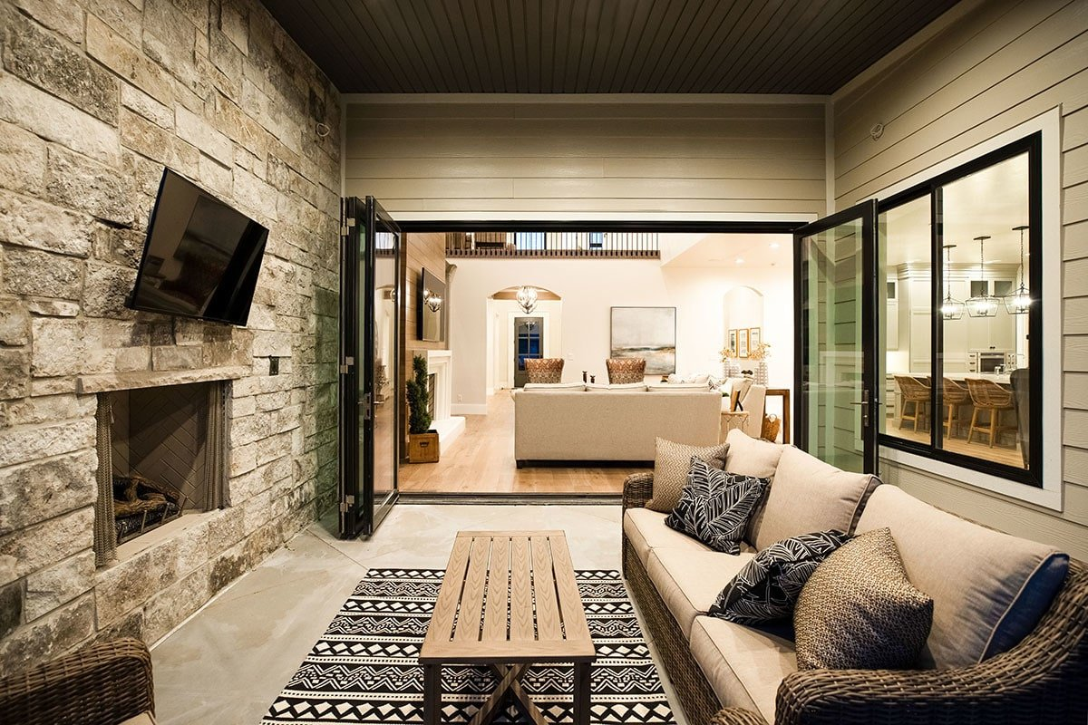 The covered patio is filled with a wicker sofa, wooden coffee table, and a TV mounted above the stone fireplace.