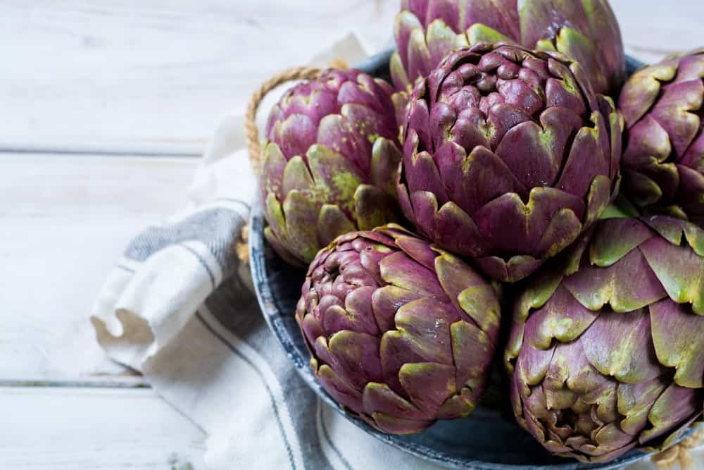 A bowl of artichokes on a striped towel above a wood plank table.