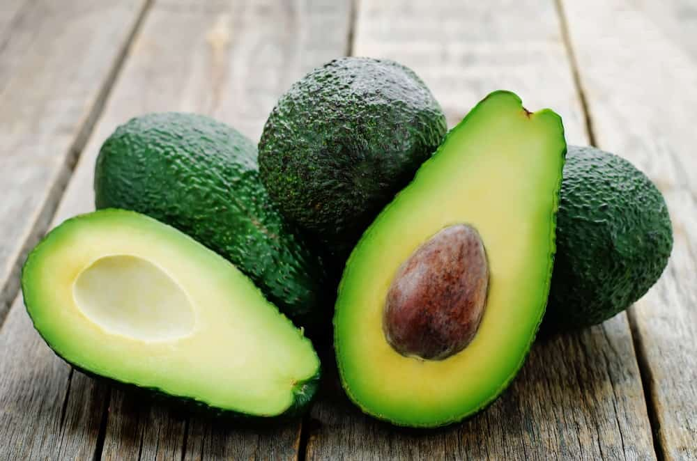Green avocados on a wood plank table.