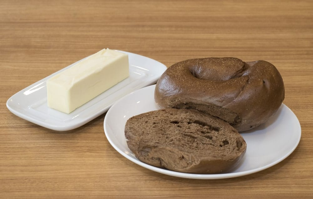 Two pumpernickel bagels on a white plate with a side of butter.